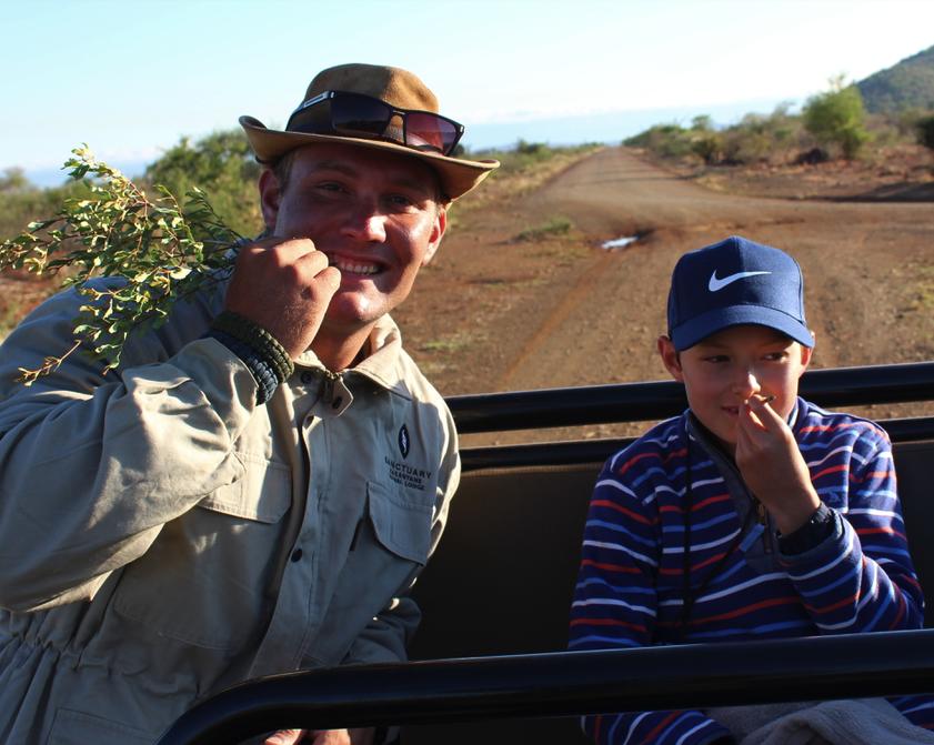 "Guide Reuben Johann Grimsell and Jack Frater sampling the ""toothpick tree"" in Madikwe Game Reserve"