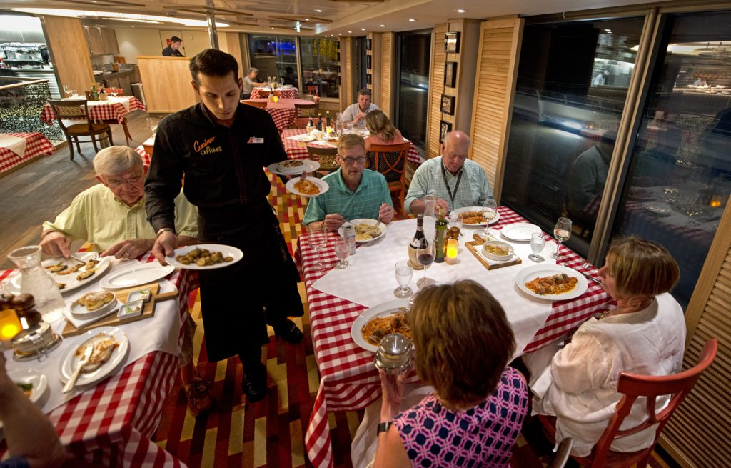 A server delivers entrées in Carnival Sunrises's Cucina del Capitano restaurant that offers delicious Italian favorites