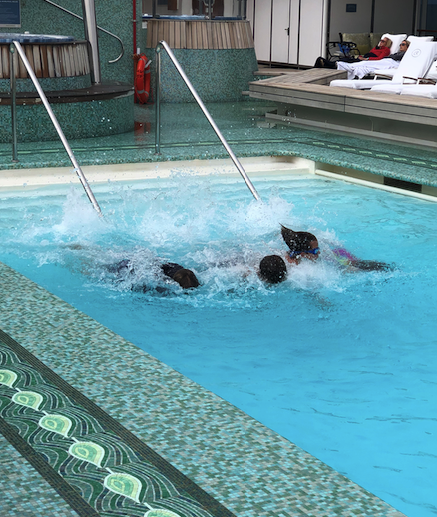 Kids having a fun day at sea in the top-deck pool of the Regent Seven Seas Mariner