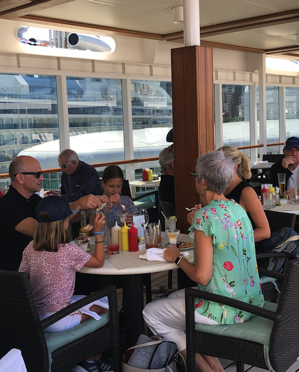 A multigen family enjoys a casual lunch on the pool deck of the Regent Seven Seas Mariner