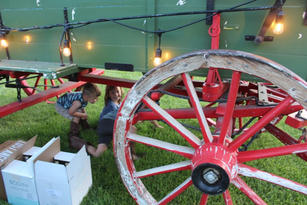 Kids playing under the wagon at the outdoor Barn Dance