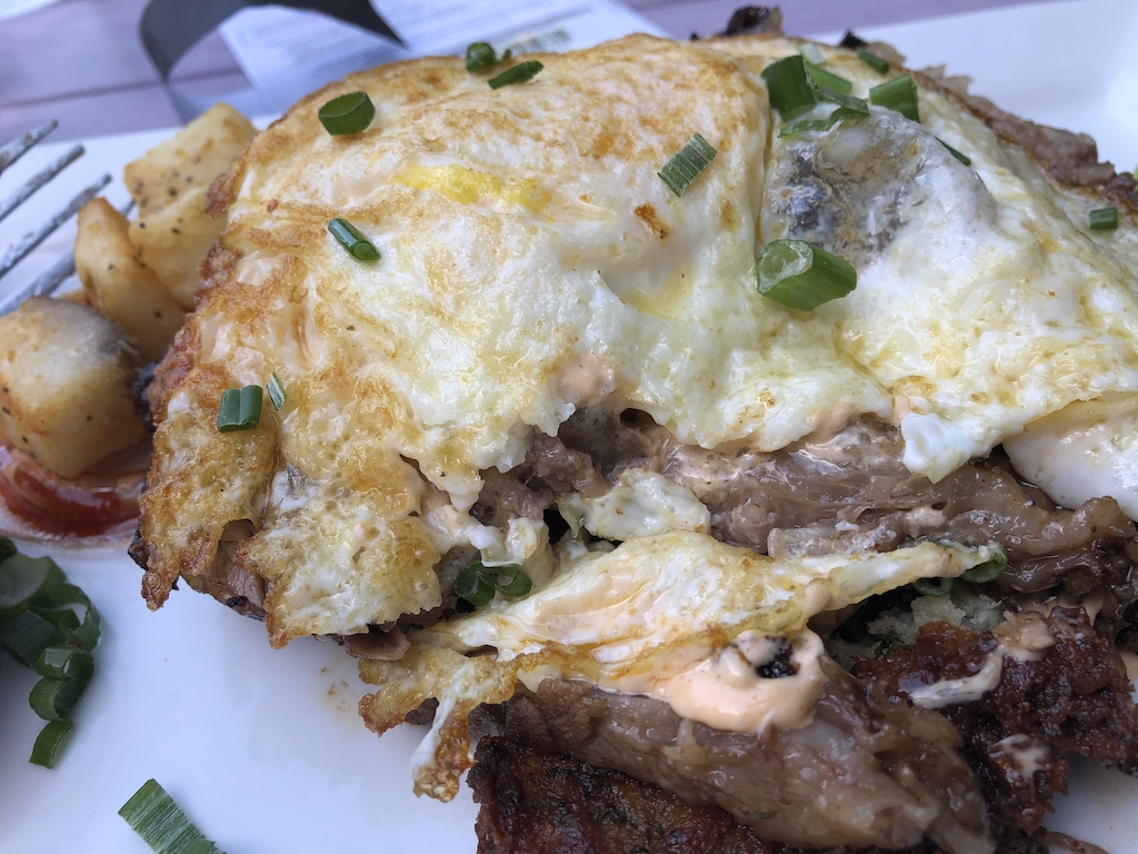 Brisket on crispy hash browns topped with egg at Toms Thumb in Scottsdale