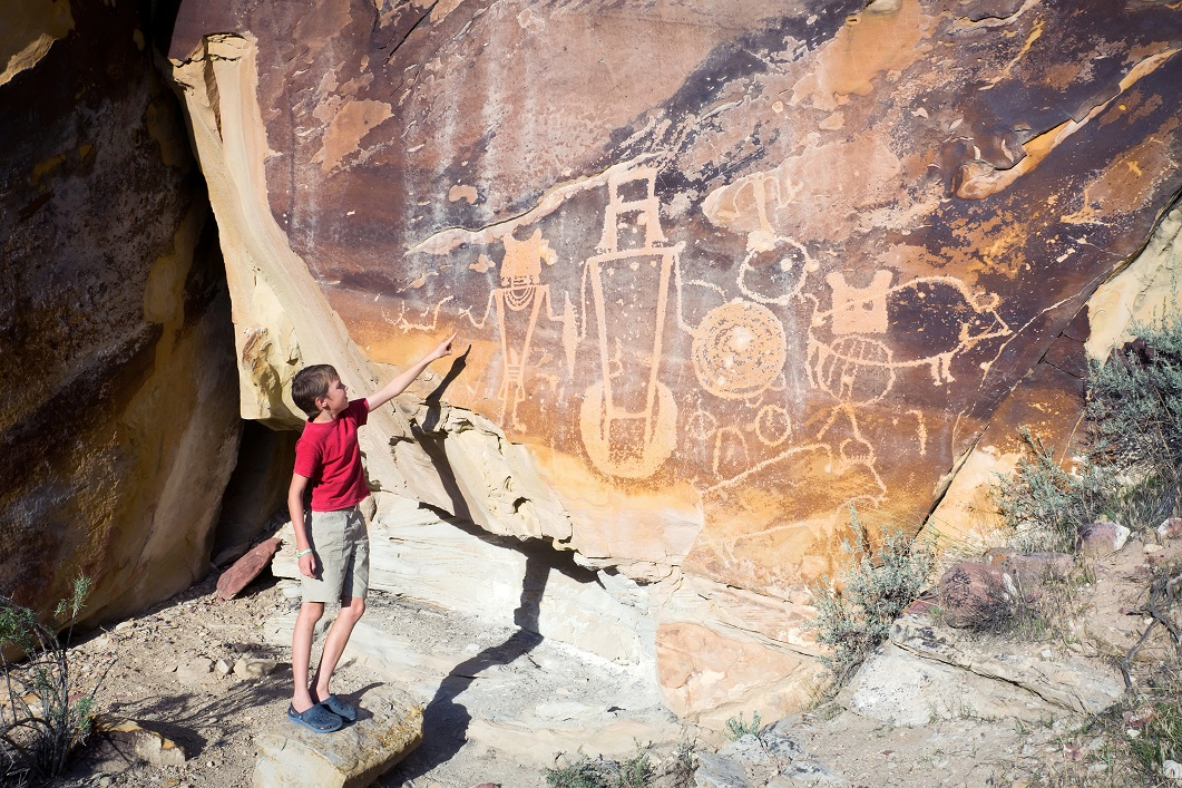 A boy shows his hand on the wall with petroglyphs. Dinosaur National Monument