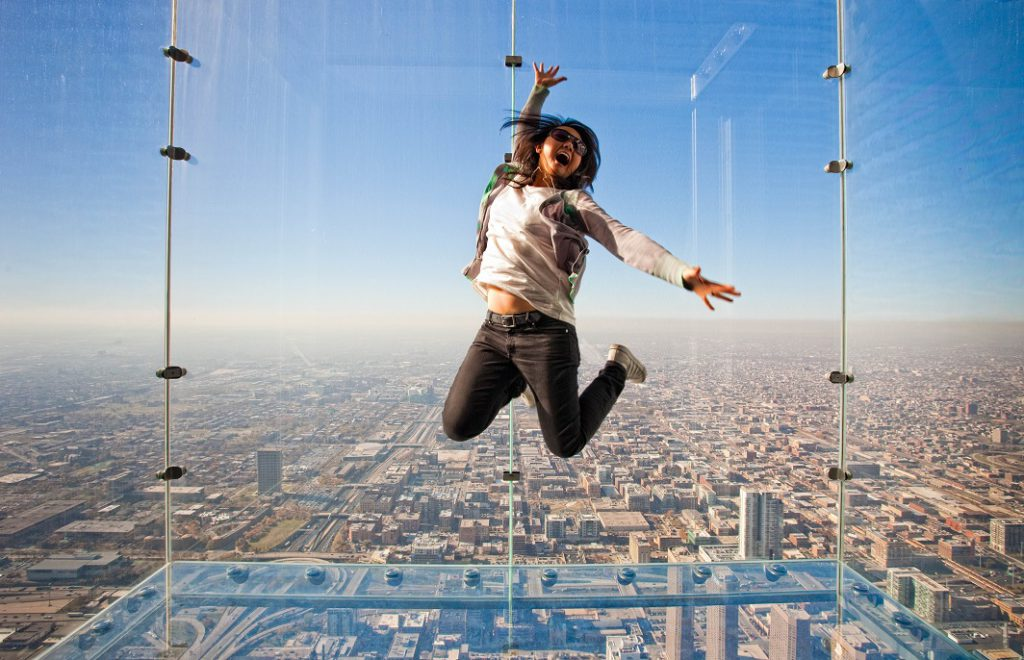 """Girl jumping on """"The Ledge"""" at Skywalk Chicago"""