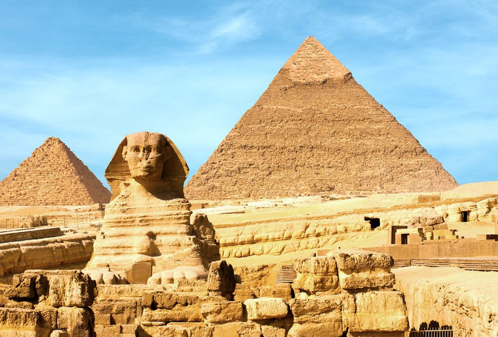 Sphinx and the large Egyptian Pyramids of Khafre, Menkaure slightly offset in front of blue sky in Giza, Cairo, Egypt.