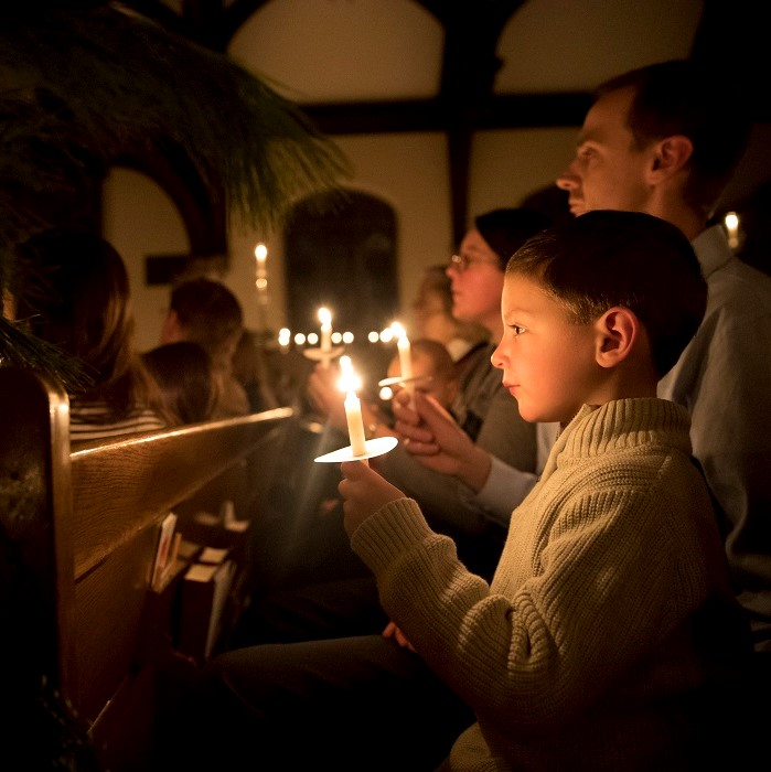 Evan Dahl, 5, of St. Paul, holds a candle while sitting with his family on Sunday, Dec. 24, 2017, in Minneapolis,