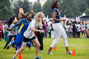 """First Lady Michelle Obama runs at an activity station during a """"Let's Move! London"""" event at Winfield House in London"""