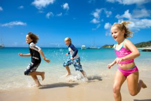 Kids romping on the calm beach at Curtain Bluff