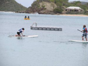 Kids try standup paddleboards on calm beach at Curtain Bluff in Antigua