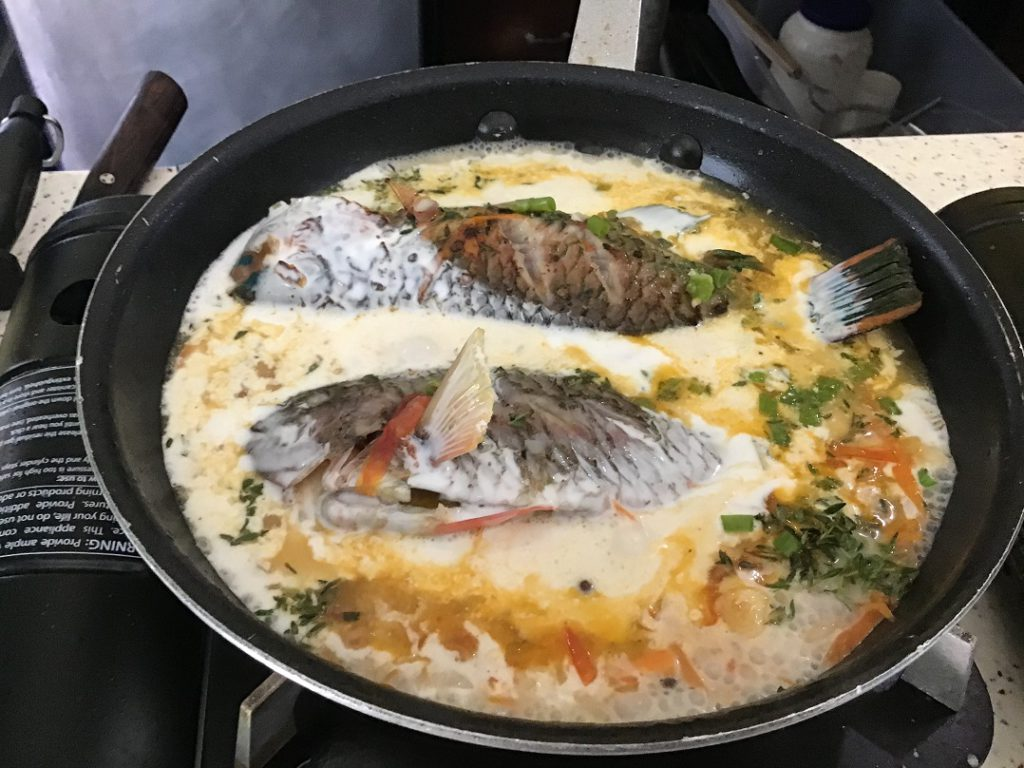 The fish finishing up in the pan of Jamaican curry sauce