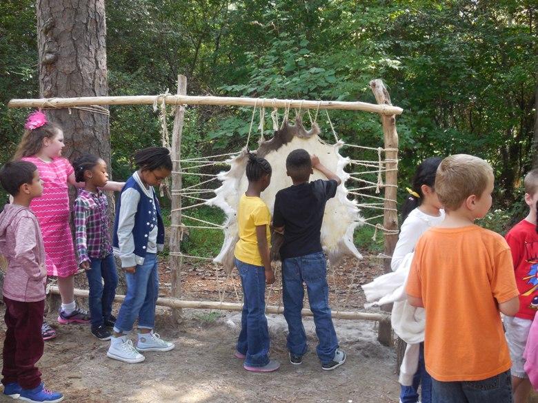 Kids scraping deer hide at Jamestown Settlement