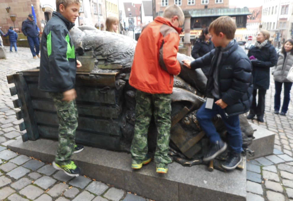 River cruise kids clambering on giant hare sculpture in Nuremberg