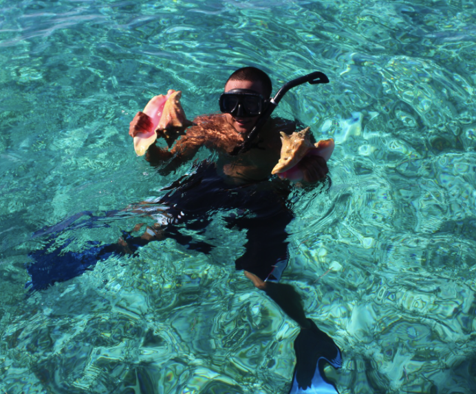 Carlos Cardova produces two nice-sized conch from Belize's barrier reef
