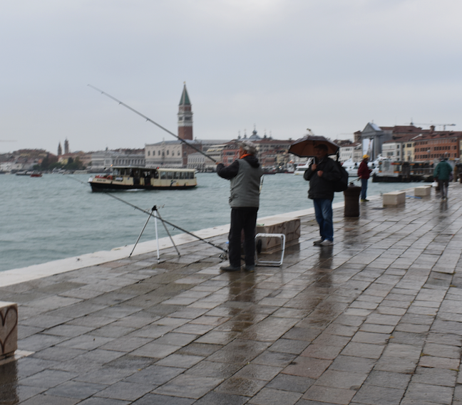 Locals fishing in the rain in Venice