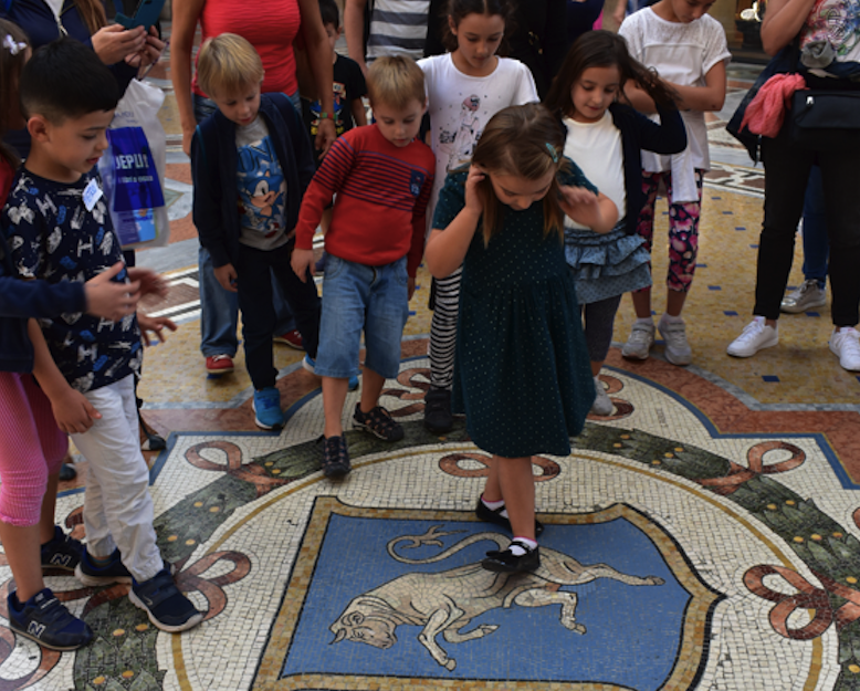 Kids twirling on the bull mosaic in the Milan Galleria