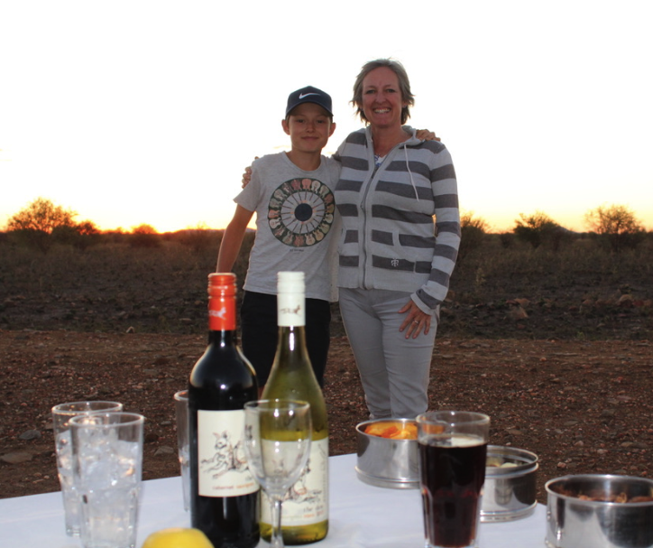 "Jack Frater and his mom Jo Prater enjoying a ""sundowner"" on safari in Madikwe Game Reserve"