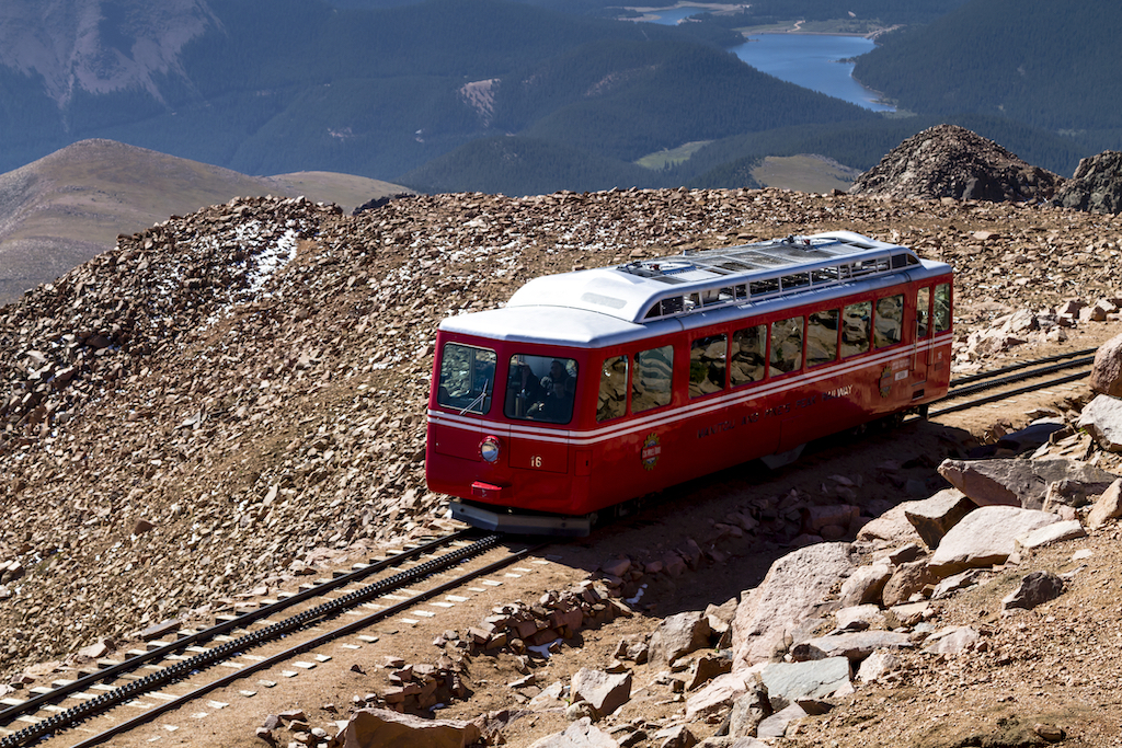 Pikes Peak Cog Railway car leaving the top of Pikes Peak mountain top in Colorado on sunny summer morning.