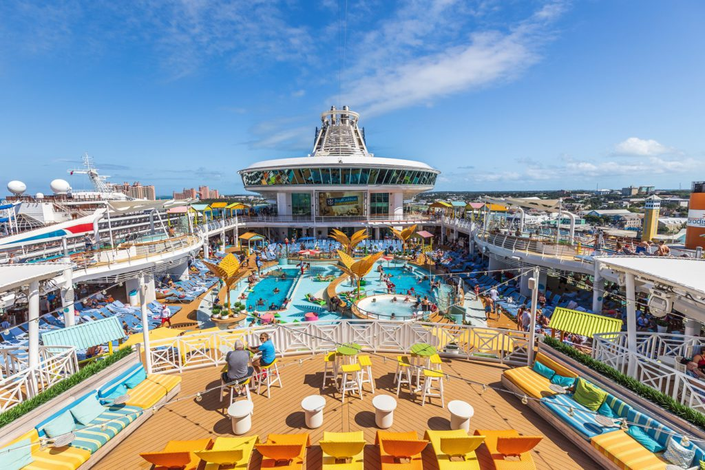 The top of a Royal Caribbean cruise ship with a balcony looking down over a pool with people and lounge chairs.