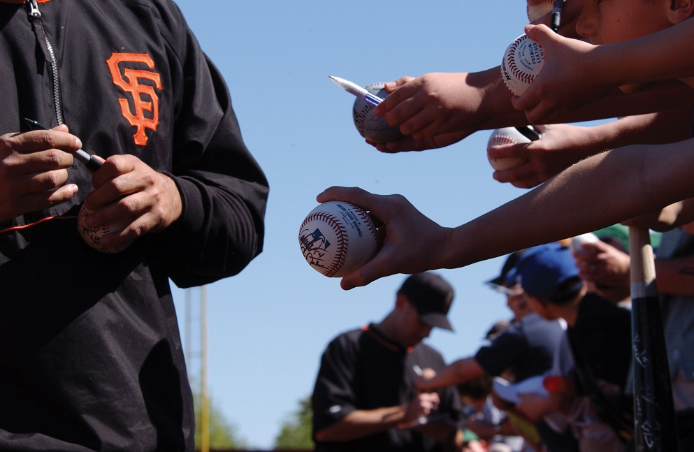 A Giants player signs autographs at Scottsdale Stadium