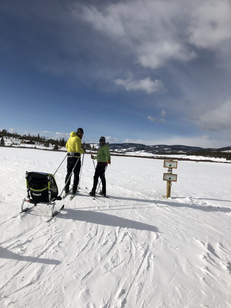 A couple on the Nordic trails at Devil's Thumb Ranch with their 7-month-old in tow