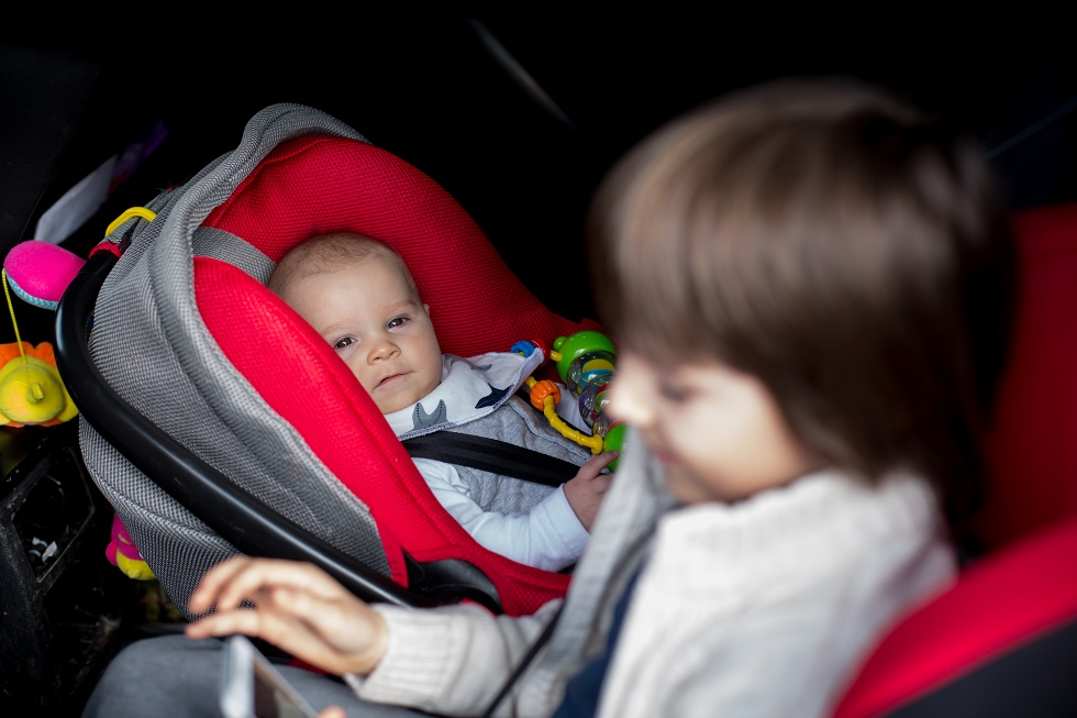 Little baby boy and his older brother, traveling in car seats, g