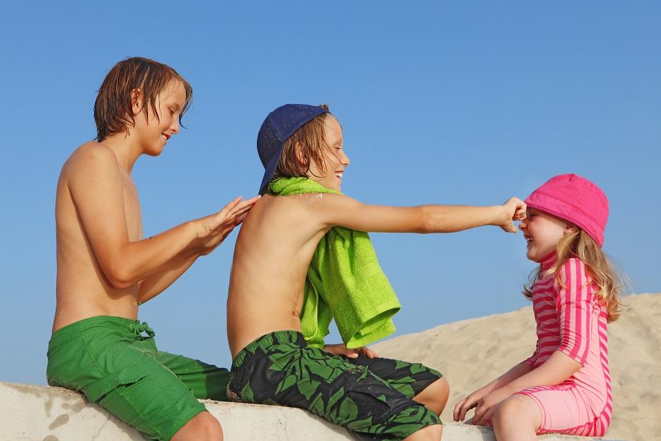 Children on beach applying sun protection