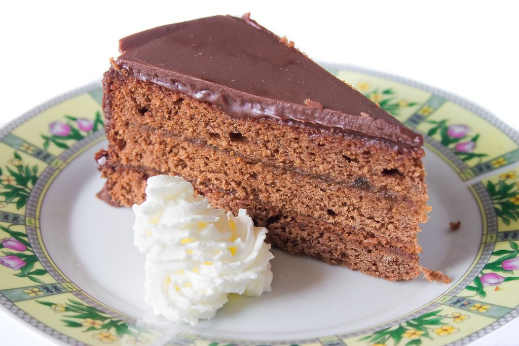 Slice of traditional austrian Sacher Torte cake with whipped cream