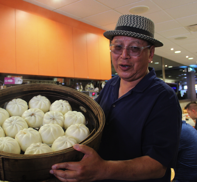 Robert Sung holding pastry balls at New Town Chinese Bakery in Vancouver