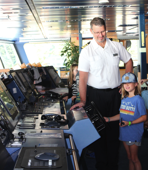 Captain Palm shows the ship's wheel to a young crew member