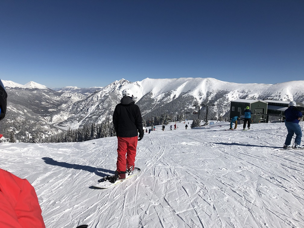 Snowboarder gets ready to carve Copper Mountain on bluebird day