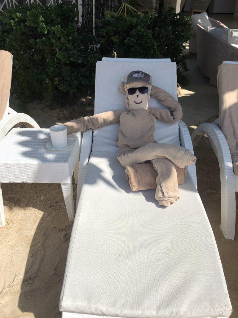 The towel guy lounges on the beach at Sundown Villa