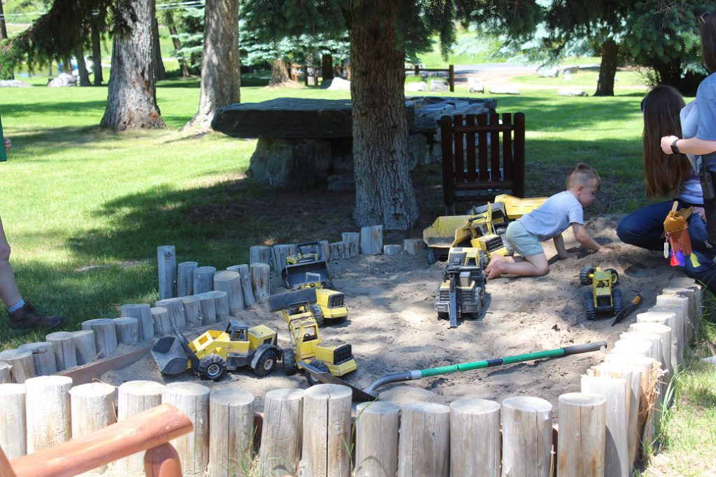 Youngsters excavating for dinosaurs in sandbox at Flathead Lake Lodge