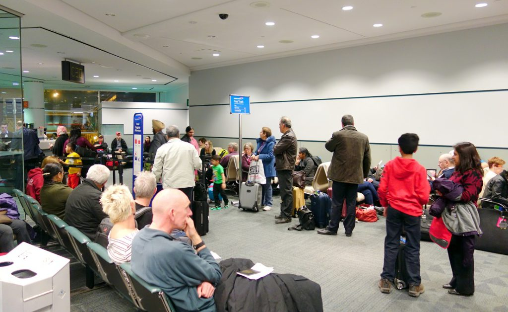 People lining up at a Toronto Pearson Airport gate.