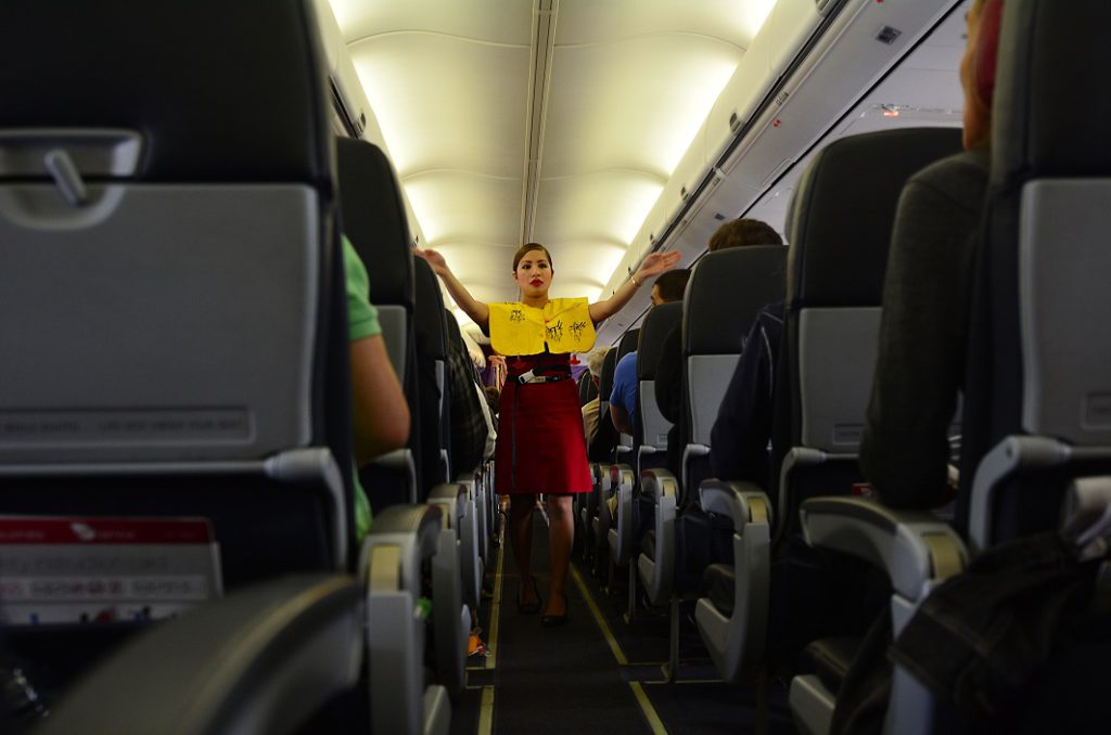 Flight Attendant giving safety briefing, which most passengers seem to ignore