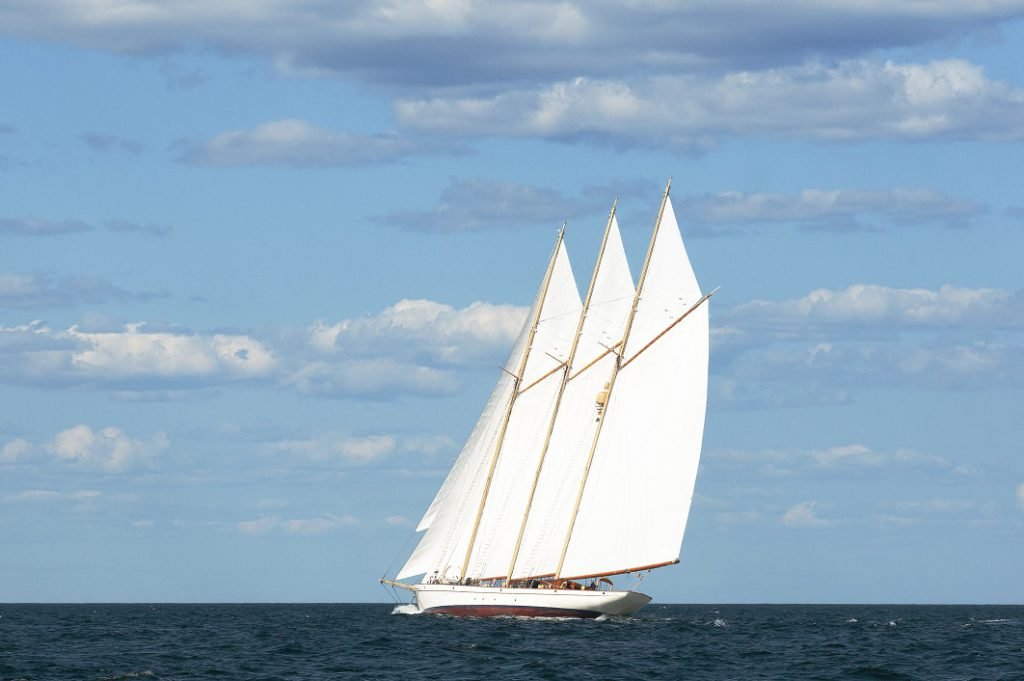 Authentic schooner windjamming sailing vessel with three masts cruises by on a warm summer day along the Maine Seacoast. Windjamming is a favorite attraction for tourists.