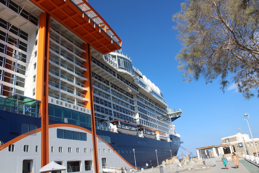 """The Celebrity Apex docked in Mykonos - Orange structure is the """"Magic Carpet"""" lounge that goes up and down the side of the new ship"""