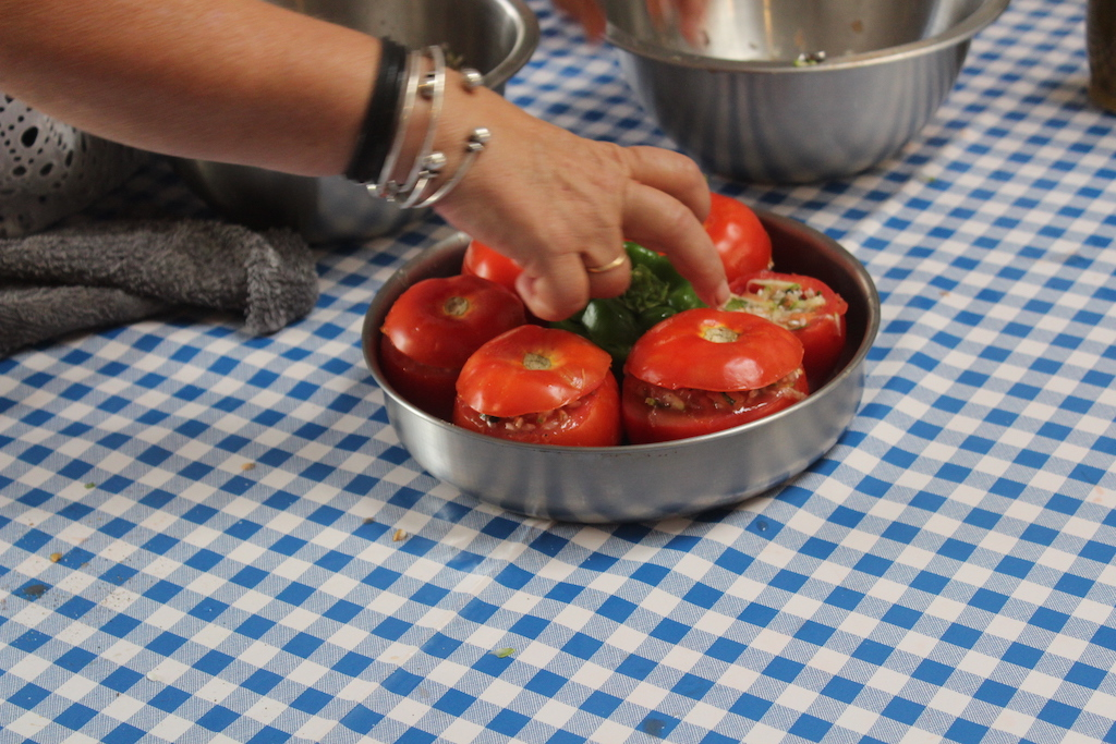 Preparing tomatoes and peppers stuffed with rice, garlic and mint